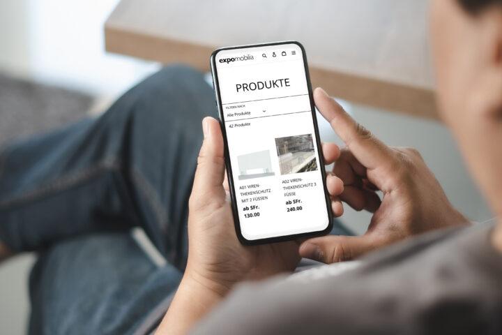 Man mit Smartphone in der Hand uns scrollt durch den Online-Shop.